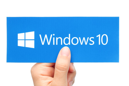 programm: KIEV, UKRAINE - AUGUST 18, 2015:Hand holds Windows 10 logotype printed on paper. Windows 10 is an operating system developed by Microsoft
