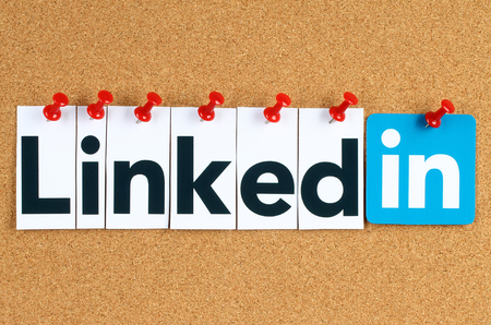 Kiev, Ukraine - October 07, 2015: Linkedin logo sign printed on paper, cut and pinned on cork bulletin board. Linkedin is a business social networking service.
