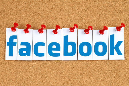 Kiev, Ukraine - October 07, 2015: Facebook logo sign printed on paper, cut and pinned on cork bulletin board. Facebook is a well-known social networking service.
