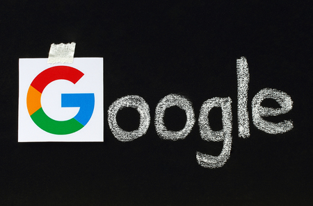 google plus: Kiev, Ukraine - September 02, 2015:New Google logotype printed on paper, cut and pasted on blackboard with chalk finish writing.Google is USA multinational corporation.