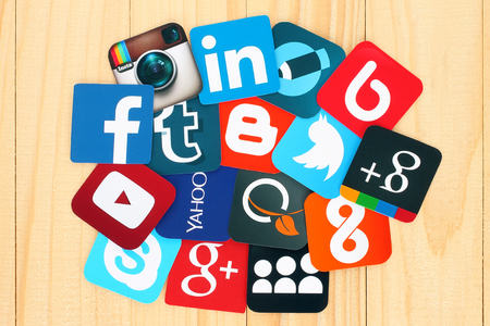 Kiev, Ucrania - 01 de julio de, 2015: famosos iconos de redes sociales como: Facebook, Twitter, Blogger, Linkedin, Tumblr, Myspace y otros, impresos en papel y colocados alrededor en el fondo de madera.