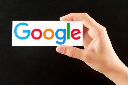 キエフ, ウクライナ - 2002 年 9 月、2015:Hand は、新しい Google ロゴ黒板背景に紙に印刷を保持しています。Google は米国の多国籍企業です。