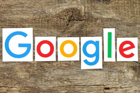Kiev, Ukraine - January 12, 2016:New Google logotype printed on paper, cut and placed on old wood.Google is USA multinational corporation specializing in Internet-related services Imagens - 50730352