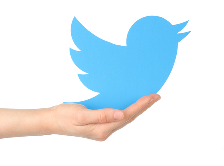 Kiev, Ukraine - January 15, 2016: Hand holds twitter logotype bird printed on paper. Twitter is an online social networking service that enables users to send and read short messages. 報道画像