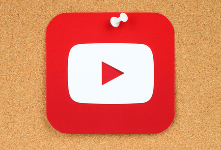 Kiev, Ukraine - February 10, 2016: YouTube logotype printed on paper and pinned on cork bulletin board. YouTube is a video-sharing website Editorial