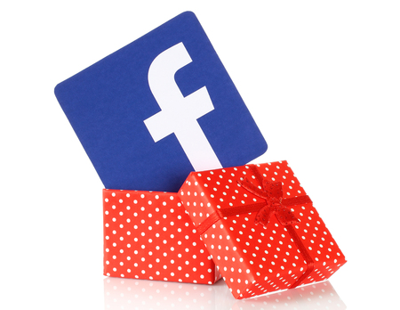 social networking service: Kiev, Ukraine - January 11, 2016: Facebook logo printed on paper and put into present box on white background. Facebook is a well-known social networking service.