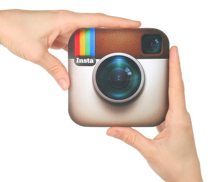 Kiev, Ukraine - January 15, 2016: Hands hold Instagram logo printed on paper on white background. Instagram is an online mobile photo-sharing, video-sharing service Редакционное