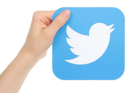 Kiev, Ukraine - January 15, 2016: Hand holds twitter icon printed on paper. Twitter is an online social networking service that enables users to send and read short messages.