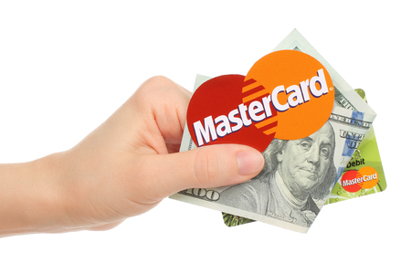 mastercard: Kiev, Ukraine - January 15, 2016: Hand holds Mastercard logo printed on paper with money and credit card on white background