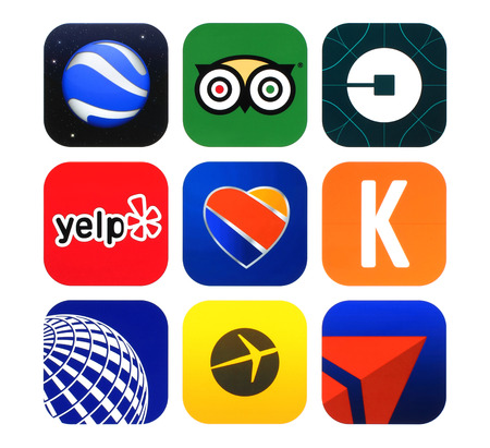 Kiev, Ukraine - February 22, 2016: Collection of popular travel icons printed on paper: Expedia, Fly Delta, Google Earth, Kayak, Southwest Airlines, TripAdvisor, Uber, Yelp and United Airlines Editorial