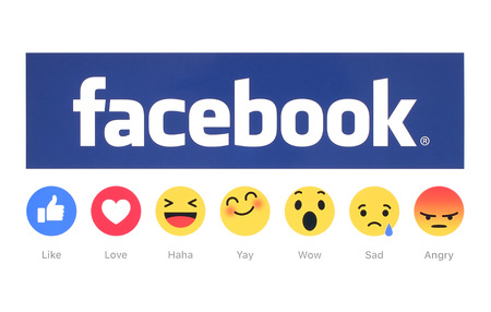 Kiev, Ukraine - February 26, 2016: New Facebook like button 6 Empathetic Emoji Reactions printed on white paper. Facebook is a well-known social networking service. Редакционное