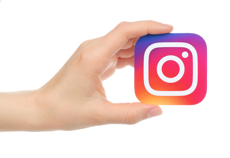 Kiev, Ukraine - May 17, 2016: Hand holds new Instagram logo printed on paper, on white background. Instagram is an online mobile photo-sharing, video-sharing service.