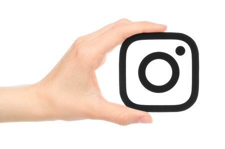 new icon: Kiev, Ukraine - May 17, 2016: Hand holds new Instagram logo printed on paper, on white background. Instagram is an online mobile photo-sharing, video-sharing service.