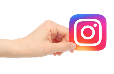 Kiev, Ukraine - May 18, 2016: Hand holds new Instagram logo printed on paper, on white background. Instagram is an online mobile photo-sharing, video-sharing service.