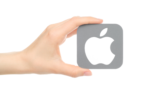 operating system: Kiev, Ukraine - May 18, 2016: Hand holds popular operating system logo printed on paper Apple ios. Apple Inc. is an American multinational technology company