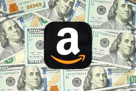 キエフ, ウクライナ - 2016 年 6 月 13 日: アマゾン アイコンは紙に印刷し、お金の背景上に配置します。アマゾンはアメリカの電子商取引会社です。