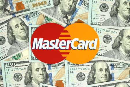 mastercard: Kiev, Ukraine - June 13, 2016: Mastercard logo printed on paper and placed on money background. MasterCard Worldwide is an American multinational financial services corporation Editorial