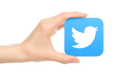 enables: Kiev, Ukraine - May 18, 2016: Hand holds twitter icon printed on paper. Twitter is an online social networking service that enables users to send and read short messages
