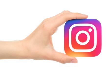 キエフ, ウクライナ - 2016 年 5 月 18 日: 手は白い背景の上の紙に印刷されたロゴマーク Instagram を保持します。Instagram は、オンライン モバイル写真の