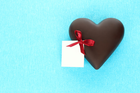 Chocolate heart with greeting card on blue background close-up