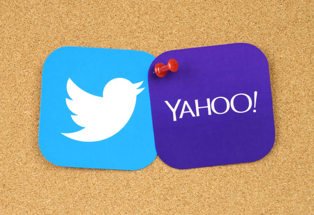 reportedly: Kiev, Ukraine - September 12, 2016: Twitter and Yahoo icons printed on paper and pinned on cork bulletin board together. Twitter reportedly held merger talks with Yahoo Editorial