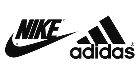 Kiev, Ukraine - September 26, 2016: Collection of popular manufactures sports shoes logos printed on paper: Nike and Adidas