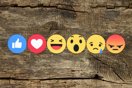 Kiev, Ukraine - February 07, 2017: Facebook like button 6 Empathetic Emoji Reactions printed on paper and placed on wooden background. Facebook is a well-known social networking service