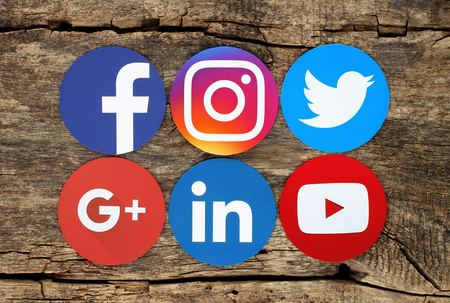 Kiev, Ukraine - March 03, 2017: Famous round social media icons such as: Facebook, Twitter, Instagram, Linkedin, Google Plus, and Youtube printed on paper and placed on wooden background