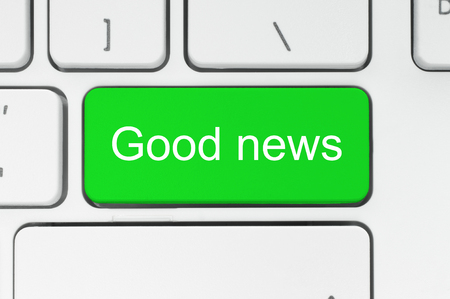 breaking: Green button with good news words on the keyboard close-up