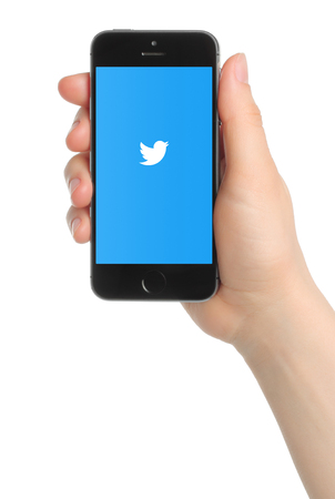 Kiev, Ukraine - March 7, 2015: Hand holds iPhone 5s Space Gray with Twitter logo on white background. Twitter is a well-known social networking service
