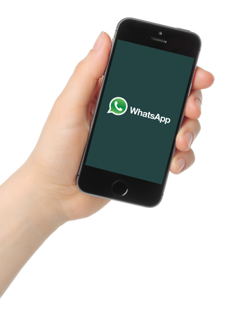 Kiev, Ukraine - March 7, 2015: Hand holds iPhone 5s Space Gray with WhatsApp logo on white background