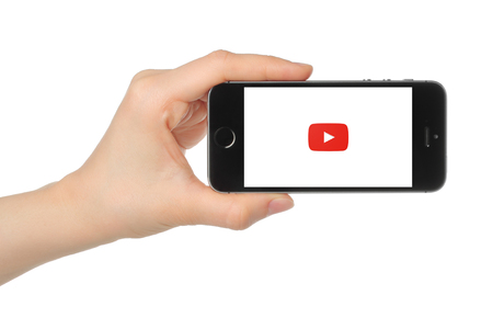 Kiev, Ukraine - March 7, 2015: Hand holds iPhone 5s Space Gray with Youtube logo on white background