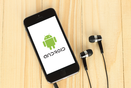 Kiev, Ukraine - May 22, 2015: iPhone with Android logotype on its screen and headphones on wooden background