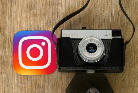 Kiev, Ucrânia - 4 de setembro de 2017: logotipo Instagram impresso em papel e colocar perto de câmera fotográfica retro em fundo de madeira. Instagram é um aplicativo e serviço de compartilhamento de fotos móvel