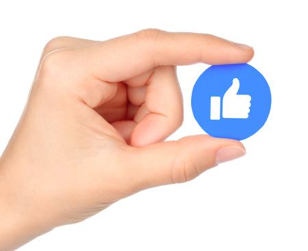 Kiev, Ucrânia - 04 de setembro de 2017: A mão possui Facebook Like Empathetic Emoji Reaction, impresso em papel. O Facebook é um conhecido serviço de rede social Editorial