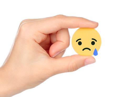 Kiev, Ucrânia - 04 de setembro de 2017: A mão segura Facebook Sad Empática Emoji Reacção, impressa em papel. O Facebook é um conhecido serviço de rede social Editorial