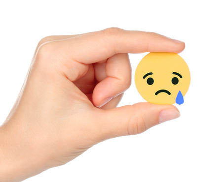 Kiev, Ukraine - September 04, 2017: Hand holds Facebook Sad Empathetic Emoji Reaction, printed on paper. Facebook is a well-known social networking service