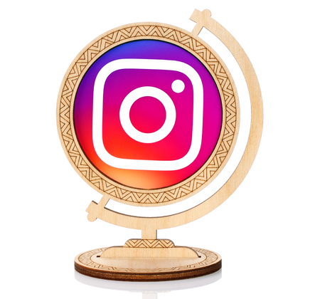 Kiev, Ukraine - March 03, 2017: Instagram circle icon printed on paper and placed into wooden globe on white background. Instagram is a mobile, desktop, and Internet-based photo-sharing application Editorial