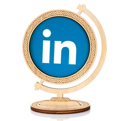 Kiev, Ucrânia - 03 de março de 2017: ícone de círculo do LinkedIn impresso em papel e colocado no globo de madeira no fundo branco. O LinkedIn é um serviço de redes sociais orientado a negócios e emprego
