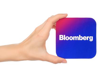 Kiev, Ucrânia - 04 de setembro de 2017: A mão segura o ícone de Bloomberg impresso em papel. Bloomberg é um acesso a notícias globais sobre negócios e finanças