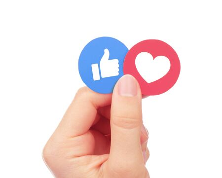 Kiev, Ukraine - September 04, 2017: Hand holds Facebook Like and Love Empathetic Emoji Reactions, printed on paper. Facebook is a well-known social networking service