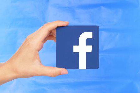 Kiev, Ukraine - September 4, 2017: Hand holds Facebook icon printed on paper on blue paper background. Facebook is a well-known social networking service Editorial