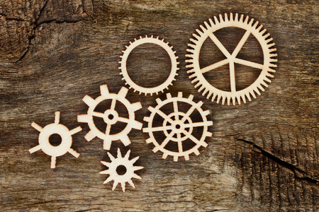 Wooden gears on wooden background close-up Imagens