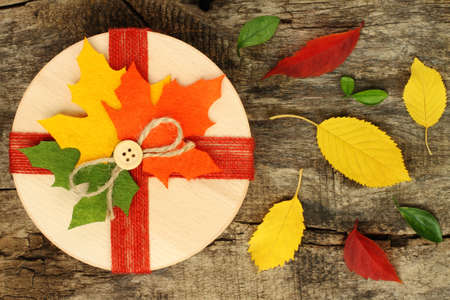 Autumn concept of present box with dried leaves on wooden backround Imagens