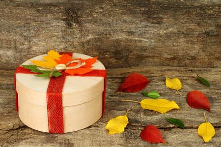 Conceito de outono da caixa presente com folhas secas em backround de madeira