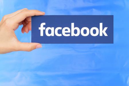 Kiev, Ucrânia - 4 de setembro de 2017: A mão segura o logotipo do Facebook impresso em papel no fundo do papel azul. O Facebook é um conhecido serviço de rede social Editorial