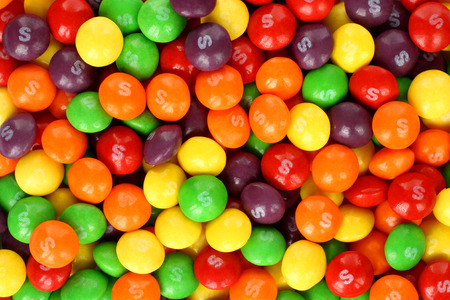 Kiev, Ukraine - September 22, 2017: Skittles multicolored fruit candies background. Skittles is a brand of fruit-flavoured sweets, currently produced and marketed by the Wrigley Company