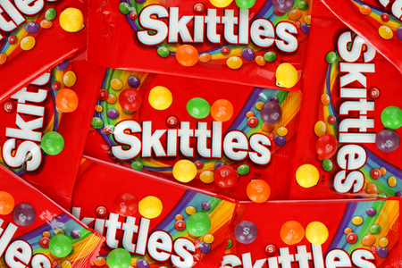 Kiev, Ukraine - September 27, 2017: Skittles multicolored fruit candies packages background. Skittles is a brand of fruit-flavoured sweets, currently produced and marketed by the Wrigley Company Editorial