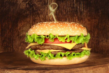 Big hamburger on wooden background close-up