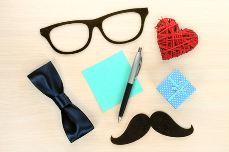 Fathers day design composition with wooden sunglasses, mustache, heart shape, bow and office supplies on wooden background